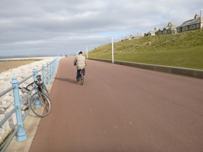 Man on a bike on the prom